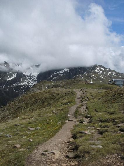 Höhenpfad auf einem Bergrücken mit Blick auf wolkenverhangene Berge.